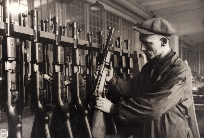 «Всё для фронта— всё для победы!». Рабочий сборочного цеха запросмотром готовых пистолетов-пулеметов перед сдачей ихприемщику. Ленинград, 25октября 1943года.